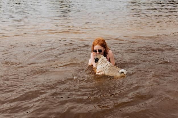 Рыжая девочка учит своего мопса плавать в реке.