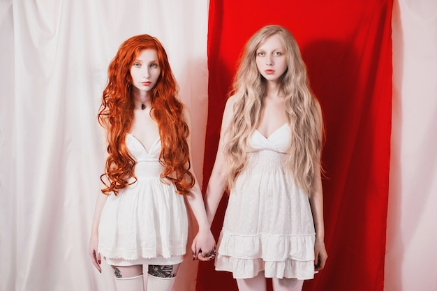 Red-haired girl touched the blonde. unity of red and white. two fabulous young girl with long curly hair. snow white and rose red. living dolls. art concept. the sisters looked at each other.