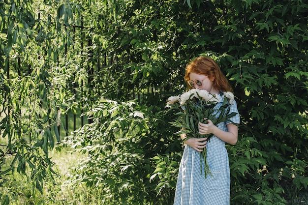 手に牡丹の花束を持つ赤い髪の少女。