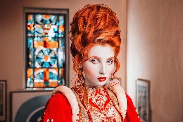 赤いドレスに青い目をした赤い髪の少女。髪型の高い女王。ヴィンテージ画像。肌が薄い女性