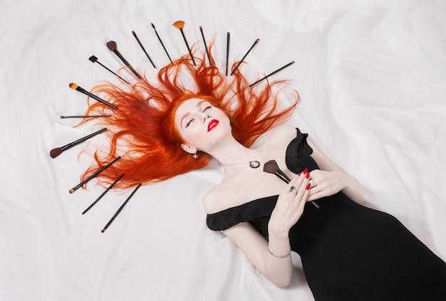 Рыжеволосая девушка с кисточками для макияжа