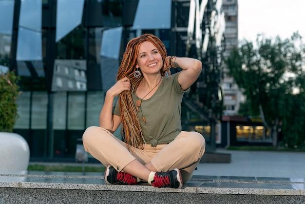 Рыжая девушка с дредами улыбается, сидя возле необычного офисного здания. девушка поправляет длинные волосы руками