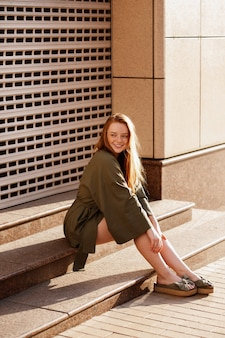 緑の服のそばかすのある赤い髪の少女は、散歩の階段に座っています。夏気分