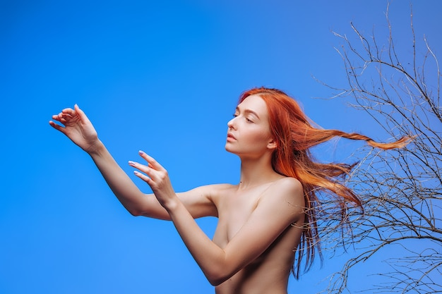 Red-haired girl with hair in dry twigs. concept hair care.