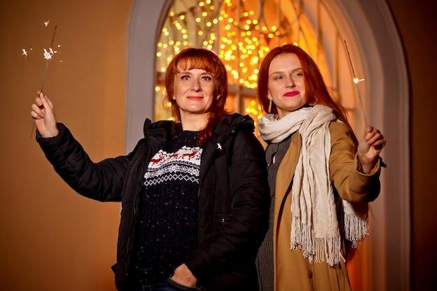 거리에서 겨울 저녁에 그녀의 어머니와 함께 나가서는 소녀