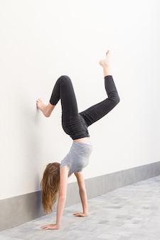 구부러진 다리로 물구나무 서기를하고있는 긴 머리를 가진 나가서는 소녀, 검은 색 바지와 밝은 벽에 회색 티셔츠를 입은 벽에 기대어있는 사람