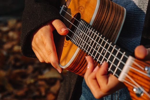 Red-haired girl with long hair plays on the ukulele in the park. school, music education concept, student learns to play the string instrument. hands of a musician, classical, melody, creativity.
