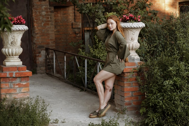 Red-haired girl with long healthy hair in green clothes in the city in the summer evening on a walk
