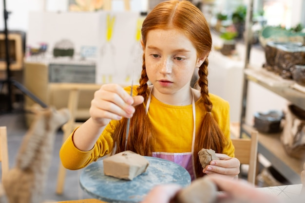 Red-haired girl with nice hairstyle sculpting clay models