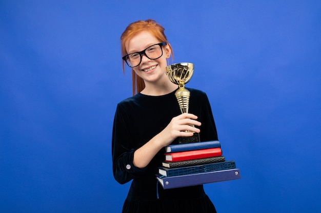 Red-haired girl with a stack of books and a victory cup on a blue studio background.