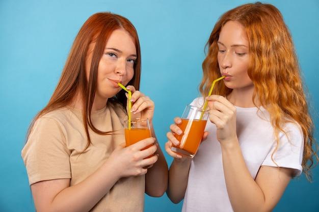 カジュアルな服装の赤毛のガールフレンドは、ストローでオレンジジュースを飲んでいます。青い壁に隔離されています。人々のライフスタイルの概念。