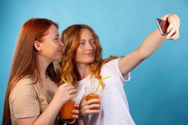 カジュアルな服装の赤毛のガールフレンドは、ストロージュースを飲み、自分撮りをします。青い壁に隔離されています。人々のライフスタイルの概念。