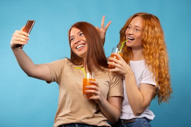 집에서 옷을 입은 빨간 머리 여자 친구가 주스를 마시고 셀카를 찍습니다.