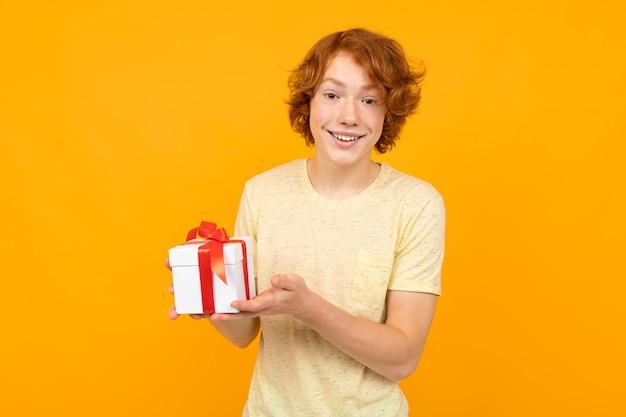 お祝いの帽子をかぶった赤髪の男がボックスに黄色のコピースペース付きのギフトを贈る
