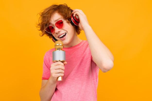 Рыжий парень певец в наушниках поет на желтом
