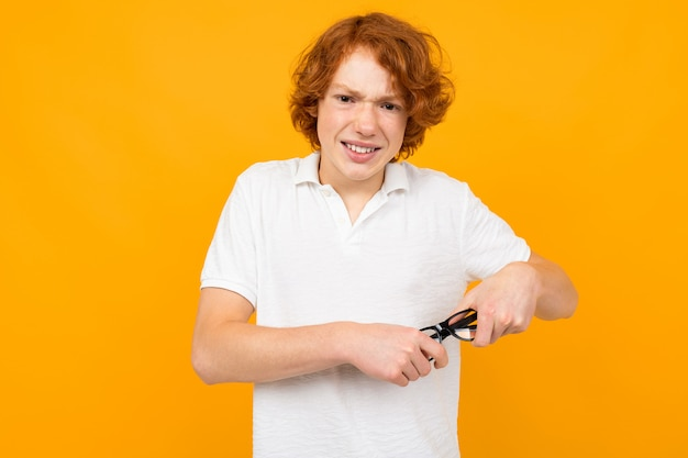 Red-haired guy in a white shirt wipes the lenses of glasses on a yellow