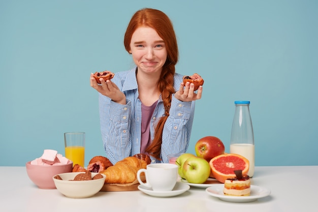 Red-haired happy funny woman has breakfast