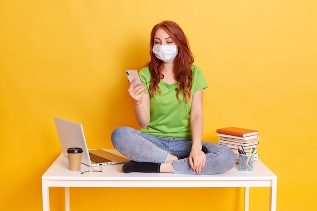 Red haired high school girl sit on table in lotus pose, uses smart phone, chatting with friends while having break, wearing jeans and green t shirt, medical mask isolated over yellow background.