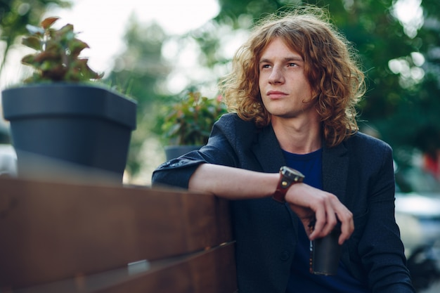 Red haired hipster man sitting on bench thinking