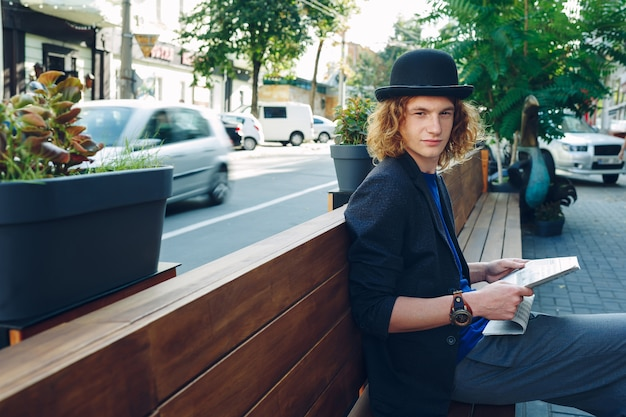 Red haired hipster man sitting on bench with newspaper
