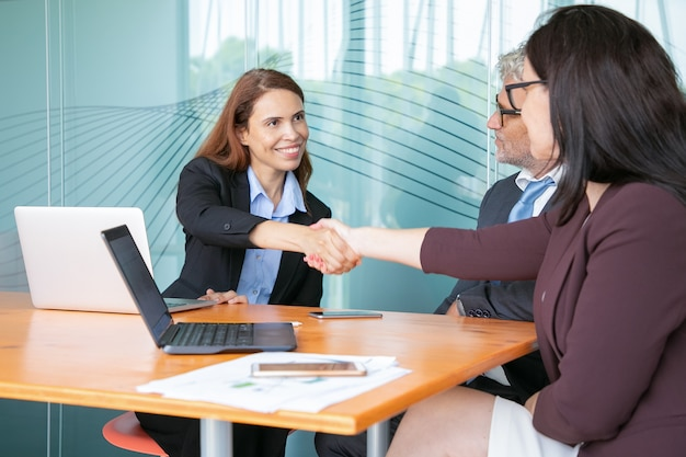 Red-haired hr manager greeting employee in conference room