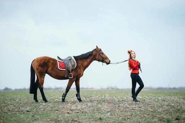산책 말과 함께 빨간 카디건과 검은 색 부츠에 나가서는 기수 소녀