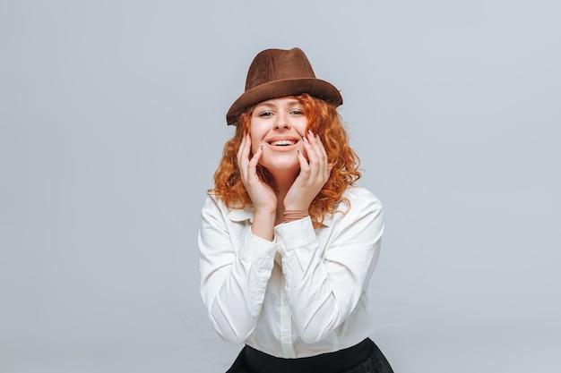 Рыжая радостная девушка в коричневой шляпе на сером фоне в белой рубашке