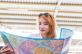 Red haired lady holding map