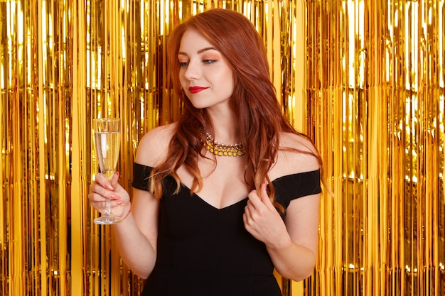 Red haired lady with champagne glass, looking dreamily aside, touching her curlers, posing against yellow wall decorated with glitter, girl wearing black dress.