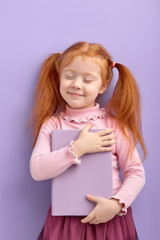 Red haired little girl isolated. sweet little girl in casual wear hug book, with eyes closed. school, education concept.