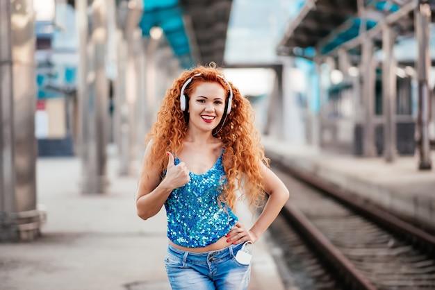 Red-haired little girl listening to music on headphones.