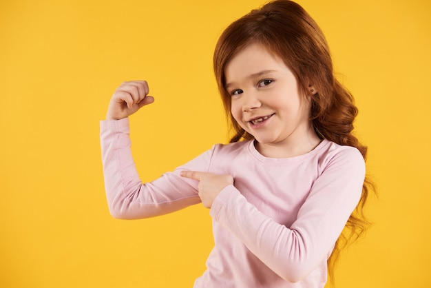 Red-haired little girl points with finger at biceps.