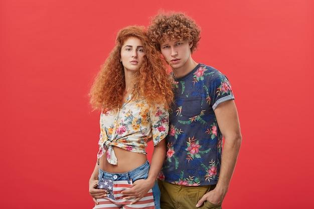 かわいい女性の近くに立っている花模様のtシャツの赤毛の男性