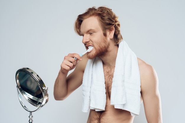 Red haired man is brushing teeth while looking in mirror.