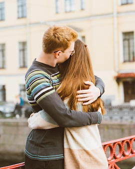 Red-haired man kisses a woman on the top of her head, a boy in a sweater