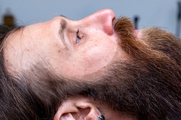 理髪店の椅子に座っている赤毛の男が、美しいトリミングされたあごひげを披露しています。