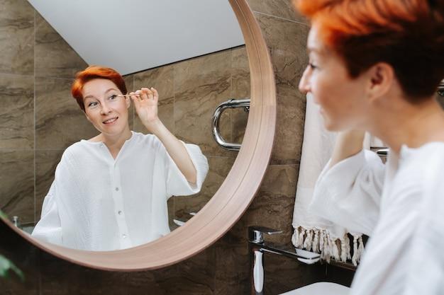 綿棒でアイメイクを修正する赤い髪の成熟した女性。彼女はバスルームの鏡の前に立っています。