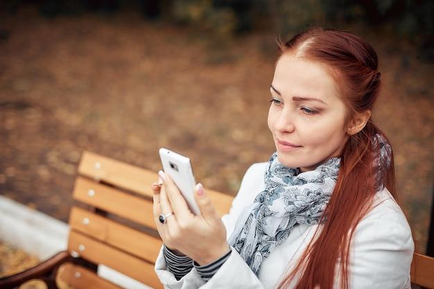 Рыжая женщина средних лет со смартфоном в руке сидит на скамейке в парке и общается в социальных сетях.