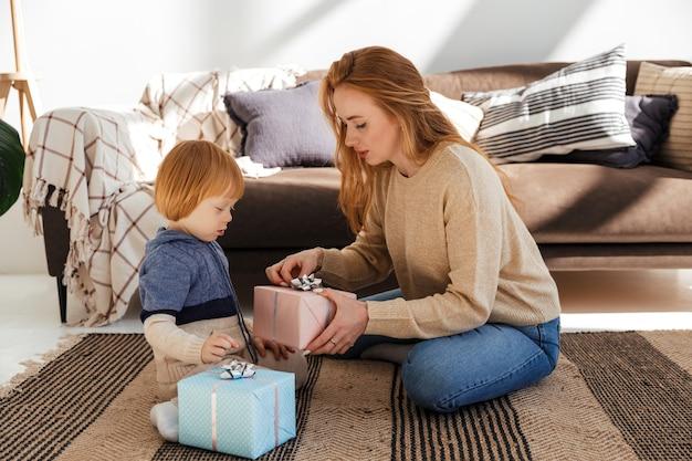 赤毛のお母さんは息子と一緒に元気にクリスマスプレゼントを準備します