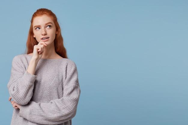 Una misteriosa giovane donna dai capelli rossi guarda di lato