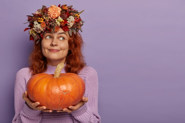 Red haired pensive content lady holds big ripe pumpkin