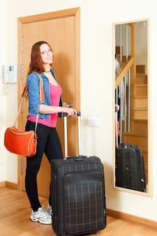 家を出る荷物とジーンズで赤毛の肯定的な女性