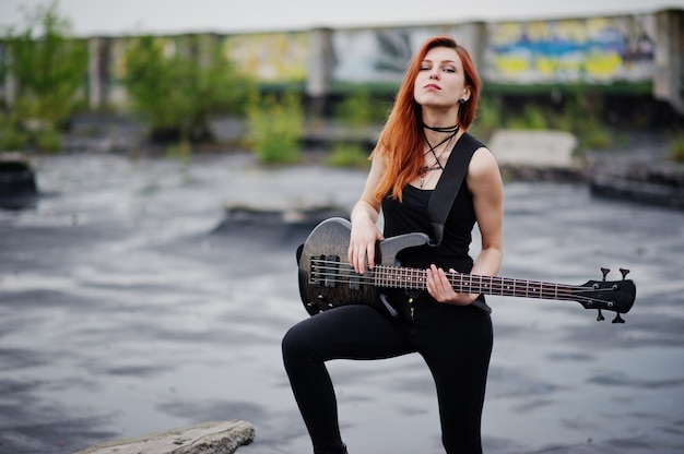 Red haired punk woman wear on black with bass guitar at the roof.