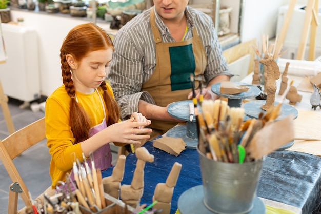 Red-haired pupil and her art teacher modeling clay figures