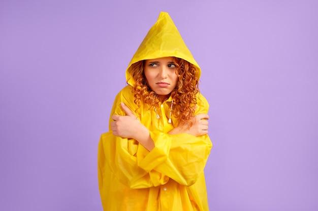 黄色いレインコートを着た赤毛の悲しい女性が凍りつき、紫に隔離された手で体を温める