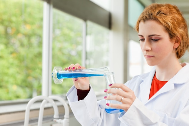 Red-haired scientist pouring liquid