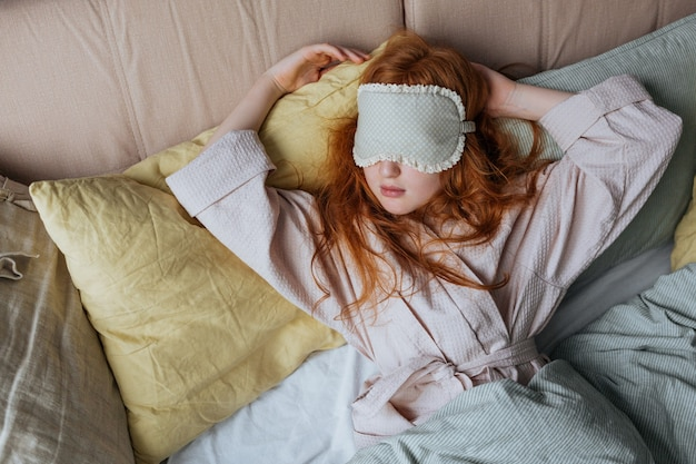 Рыжая лохматая девушка в маске для сна рано утром дремлет на кровати.