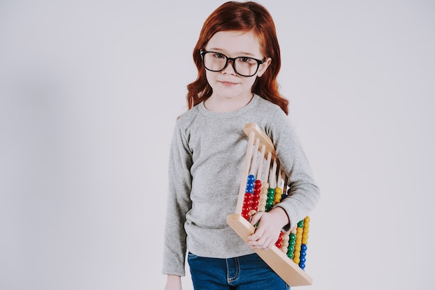 Red haired smart schoolgirl with glasses keeps abacus.