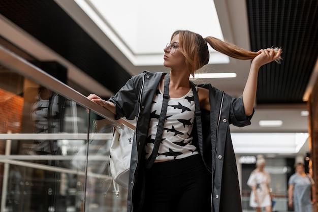 현대적인 쇼핑 센터에서 포즈를 취하는 세련 된 흰색 패턴 티셔츠에 트렌디 한 망토에 빈티지 안경에 빨간 머리 세련 된 젊은 여자. 아름다운 소녀 모델이 가게 주변을 산책합니다.