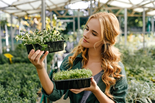 Red-haired sweet lady intently examines evergreen small plants. closeup portrait of model of european appearance in garden.